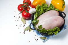 Raw chicken fillet in a cast iron frying pan with vegetables on a table, isolated on white. Selective focus. Copy space Stock Photo