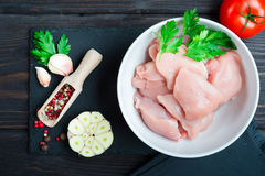 Raw chicken fillet. Raw cut chicken fillet with spices and herbs. Small pieces of meat Stock Image