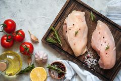 Raw chicken fillet on cutting board. With sea salt pepper and rosemary. Cooking ingredients. Fresh meat Royalty Free Stock Photo