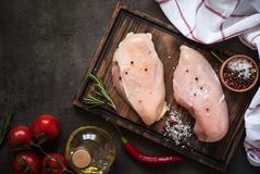 Raw chicken fillet on cutting board. With sea salt pepper and rosemary. Food background, cooking ingredients. Fresh meat Royalty Free Stock Images