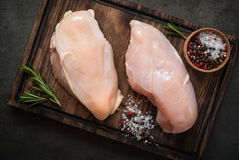 Raw chicken fillet on cutting board. With sea salt pepper and rosemary. Food background, cooking ingredients. Fresh meat Stock Image