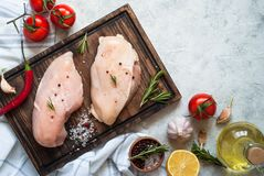 Raw chicken fillet on cutting board. With sea salt pepper and rosemary. Fresh meat. Top view Royalty Free Stock Photography
