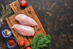 Raw chicken fillet on a cutting board with spices on a dark background. Top view, copy space, flat lay. Raw chicken fillet on a cutting board with spices on a Stock Images