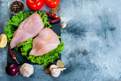 Raw chicken fillet on cutting board with spices and herbs. Royalty Free Stock Photography