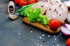 Raw chicken fillet on cutting board with spices and herbs. Food background. Cooking ingredients. Fresh meat.Top view. Copy space Stock Photo