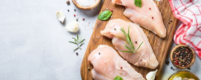 Raw chicken fillet with spices and herbs top view. Raw chicken fillet with spices and herbs on cutting board. Light stone table top view. Long banner format Stock Images