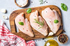 Raw chicken fillet with spices and herbs top view. Raw chicken fillet with spices and herbs on cutting board. Light stone table top view Royalty Free Stock Image