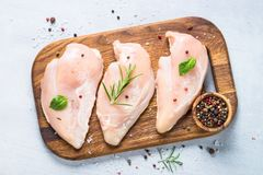 Raw chicken fillet with spices and herbs top view. Raw chicken fillet with spices and herbs on cutting board. Light stone table top view Stock Photography