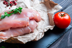 Raw chicken fillet. With spices and herbs on stone slate background Royalty Free Stock Photos