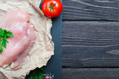 Raw chicken fillet. With spices and herbs on stone slate background Stock Images
