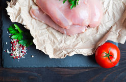 Raw chicken fillet. With spices and herbs on stone slate background Stock Photos
