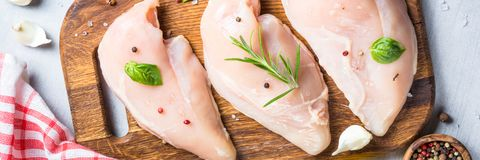 Raw chicken fillet with spices and herbs top view. Raw chicken fillet with spices and herbs on cutting board. Light stone table top view. Long banner format Royalty Free Stock Photos