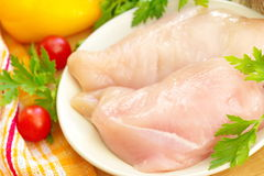 Raw chicken fillet with spices and vegetables. On the plate Stock Photos
