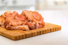 Raw chicken fillet with spices on wooden board. Close up pieces of raw chicken fillet covered with spices on wooden board ready for cooking. Selective focus Stock Photography