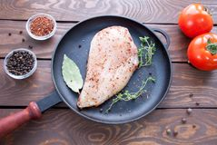 Raw chicken fillet sprinkled with herbs and spices ready to cook lies on a black iron frying pan with a laurel leaf and royalty free stock images