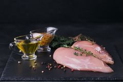 Raw chicken fillets with spices and herbs. Raw chicken fillets on black cutting board with spices and herbs. Cooking ingredients. Natural healthy food concept Royalty Free Stock Images
