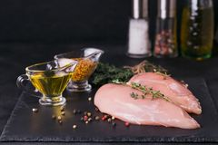 Raw chicken fillets with spices and herbs. Raw chicken fillets on black cutting board with spices and herbs. Cooking ingredients. Natural healthy food concept Stock Photo