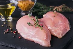 Raw chicken fillets with spices and herbs. Raw chicken fillets on black cutting board with spices and herbs. Cooking ingredients. Natural healthy food concept Royalty Free Stock Photo