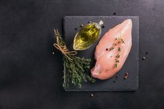 Raw chicken fillets with spices and herbs. Raw chicken fillets on black cutting board with spices and herbs. Cooking ingredients. Natural healthy food concept Stock Photos