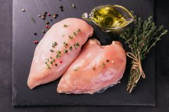 Raw chicken fillets with spices and herbs. stock photos
