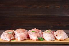 Raw chicken fillets on a cutting board against the background of a wooden table. Meat ingredients for cooking. Empty place for an Royalty Free Stock Photo
