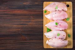 Raw chicken fillets on a cutting board against the background of a wooden table. Meat ingredients for cooking. Empty place for an Stock Photo
