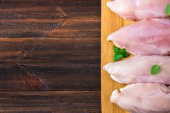 Raw chicken fillets on a cutting board against the background of a wooden table. Meat ingredients for cooking. Empty place for an. Inscription. Copy the space Stock Photo