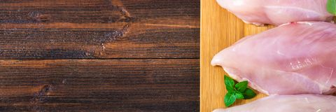 Raw chicken fillets on a cutting board against the background of a wooden table. Meat ingredients for cooking. Empty place for an. Inscription. Copy the space Royalty Free Stock Photos
