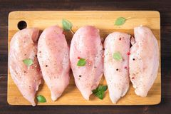 Raw chicken fillets on a cutting board against the background of a wooden table. Meat ingredients for cooking. Flat lei. Top view. Royalty Free Stock Photography