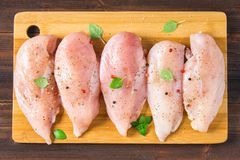 Raw chicken fillets on a cutting board against the background of a wooden table. Meat ingredients for cooking. Flat lei. Top view. Stock Photo