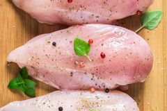 Raw chicken fillets on a cutting board against the background of a wooden table. Meat ingredients for cooking. Flat lei. Top view. Raw chicken fillets on a Stock Photos