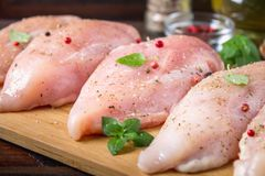 Raw chicken fillets on a cutting board against the background of a wooden table. Meat ingredients for cooking. Royalty Free Stock Image