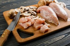 Raw chicken fillets on wooden cutting board, top view. Raw chicken fillets and mushrooms on a wooden board Stock Photos