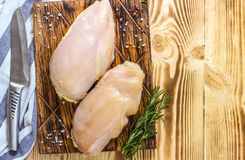 Raw chicken fillets. On wooden cutting board, top view Stock Images