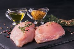 Raw chicken fillets with spices and herbs. Raw chicken fillets on black cutting board with spices and herbs. Cooking ingredients. Natural healthy food concept Royalty Free Stock Image
