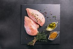 Raw chicken fillets with spices and herbs. Raw chicken fillets on black cutting board with spices and herbs. Cooking ingredients. Natural healthy food concept Royalty Free Stock Photography