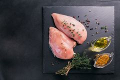 Raw chicken fillets with spices and herbs. Raw chicken fillets on black cutting board with spices and herbs. Cooking ingredients. Natural healthy food concept Royalty Free Stock Photos