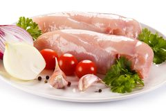 Raw chicken fillets with vegetables. On white background Royalty Free Stock Images