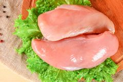 Raw chicken fillets on wooden cutting board. Raw chicken fillets on wooden cutting board Royalty Free Stock Photos