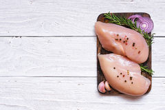 Raw chicken fillets on wooden cutting board Stock Images