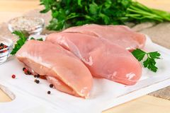 Raw chicken fillets on wooden cutting board. Raw chicken fillets on wooden cutting board Royalty Free Stock Photography