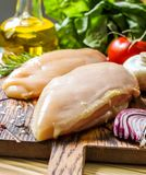 Raw chicken fillets. On wooden cutting board, selective focus Royalty Free Stock Photos