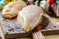 Raw chicken fillets. On wooden cutting board, selective focus Stock Images