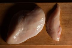 Raw chicken fillets on wooden cutting board, top view. deep shadows Royalty Free Stock Photos