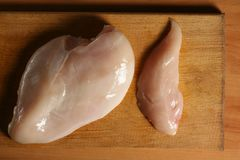 Raw chicken fillets on wooden cutting board, top view. Stock Image