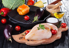 Raw chicken fillets on wooden cutting board, with vegetables. And pan grill Royalty Free Stock Image