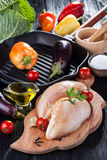 Raw chicken fillets on wooden cutting board, with vegetables. And pan grill Stock Photo