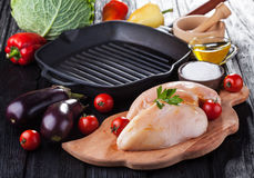 Raw chicken fillets on wooden cutting board, with vegetables. And pan grill Royalty Free Stock Photography