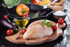 Raw chicken fillets on wooden cutting board, with vegetables. And pan grill Stock Photos