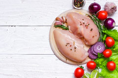 Raw chicken fillets on wooden cutting board with vegetables. Pepper, rosemary, onion and garlic. top view with copy space Stock Photography